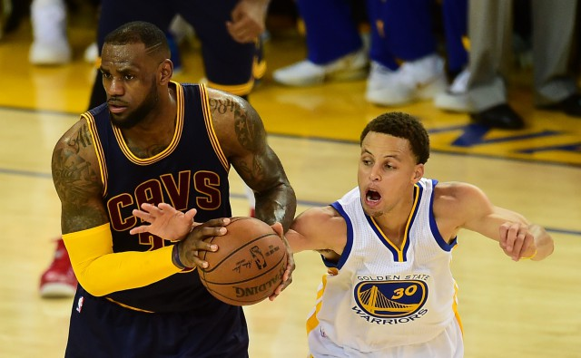 Stephen Curry (R) of the Golden State Warriors attempts to steal the ball from LeBron James (L) of the Cleveland Cavaliers during overtime in Game 1 of the 2015 NBA Finals in Oakland, California on June 4, 2015. The Warriors defeated the Cavaliers 108-100 in overtime. AFP PHOTO / FREDERIC J. BROWN (Photo credit should read FREDERIC J. BROWN/AFP/Getty Images)